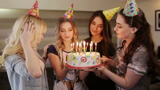girlfriend to birthday girl blows out the candles on the cake