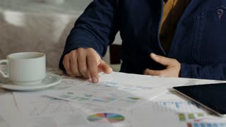 good-looking businessman working whis graphics and charts in coffee shop