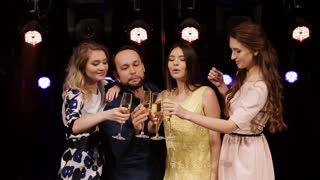 group of friends at a party fun, drinking champagne, say toasts and dancing