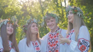 Group of young people in national costumes Slavic celebrate the summer solstice. A group of girls and boys talking and laughing at the festival.