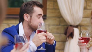 Handsome man drinking red wine and talking to girls in restaurant.