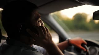 handsome young man talking on mobile phone while driving his car . Risky, reckless driver bad habits. Traffic safety rule violation lack of attention concept