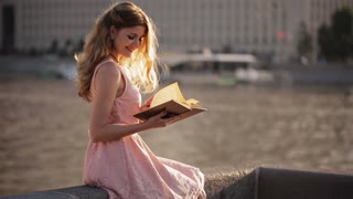 Happy girl reading a book on the waterfront at sunset