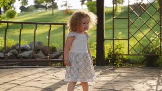 Happy little curly girl running in the park. slow motion video