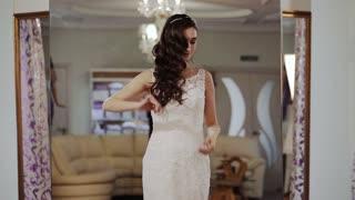 happy woman in a wedding dress walks catwalk in wedding salon
