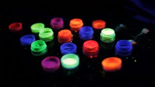 Jars with colored fluorescent powder in ultra-violet light