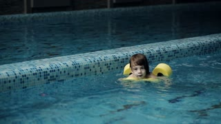 Little boy swimming in the pool at the leisure center