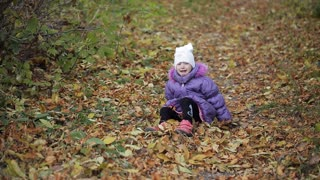 little girl fell down and crying in autumn park