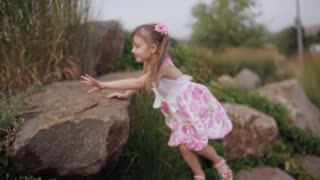 little girl in a summer dress climbing a mountain of stones