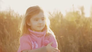 little girl in the rays of the setting sun