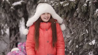 little girl laughing and throwing snow