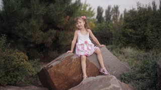 little girl sitting on a large rock in nature sings and smiles