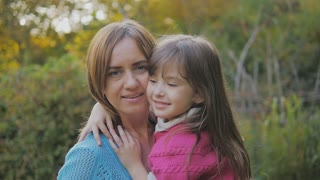 little girl with long hair laughs and hugs mom by the neck. happy mother and daughter laughing and whirl. slow-motion