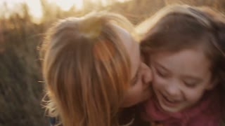 little girl with mother laughing and kissing in the sunset light