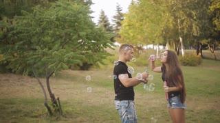 Love couple blowing the soap bubbles