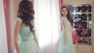 Lovely woman admires into the mirror to choose a dress in a trendy salon