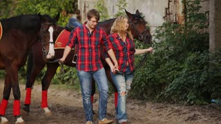 loving couple on a walk in the park with horses
