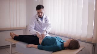 Male doctor makes palpation of the abdomen of the patient. The girl lies on a couch in the doctor's office.
