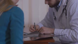 Male doctor writing rx prescription for female patient