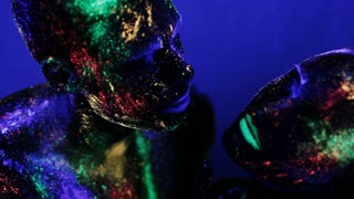man and woman in makeup glow in ultraviolet light