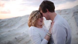 man and woman kiss background sand pit