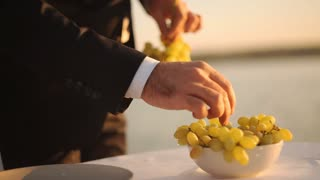 man preparing for a romantic dinner, putting grapes in a bowl