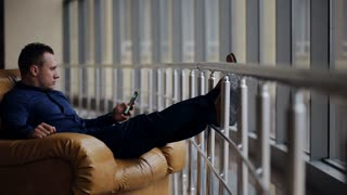 Man relaxing in his chair and enjoying the view from office window