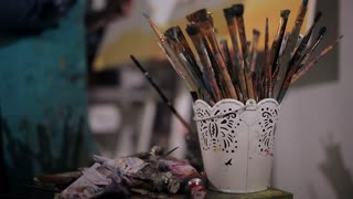 many artist brushes and tubes of paint. The artist paints a picture.