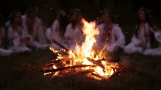 Midsummer night. Young people in Slavic clothes sitting near the bonfire.