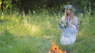 Midsummer. Woman weaving a wreath near the fire.