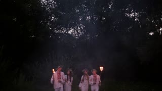 Midsummer. Young people in the same Slavic costumes are holding torches with fire.