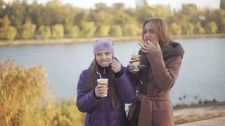 Mom and daughter in the park drinking coffee and cocoa with marmalade