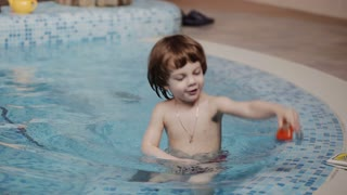 Mom and son playing in the pool with toys