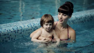 Mom teaches a child to swim in the pool. Mom and son swimming in the pool