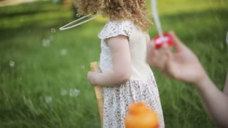Mother and daughter blowing bubbles outdoors in summer sunshine