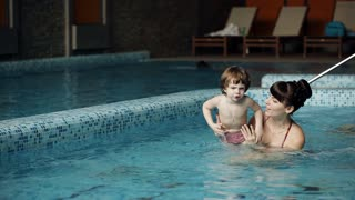 Mother and son in the pool. Young mother teaches her 3-year-old son to swim