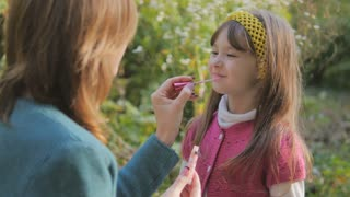 Mother makes up lips with lipstick to the daughter and kisses. Happy loving family. sunny spring day in the park