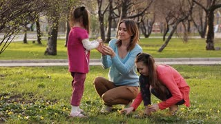 mother sniffs the flowers that she gave little daughter