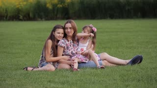 mother with two daughters smiling and having fun on the grass in the park