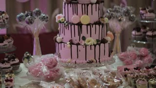 multi-tiered wedding cake with cupcakes and macaroon