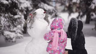 parents and children playing in the snow. Mom and daughter sculpt of snow in the winter woods.