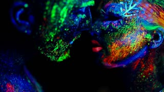 People are colored fluorescent powder. Unreal love in ultraviolet light.