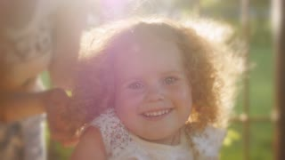 Portrait of beautiful curly girl in sunset light. Happy curly girl