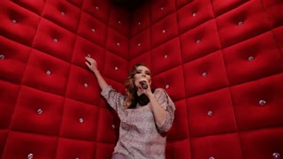 pretty girl with a microphone singing karaoke bar on a red background