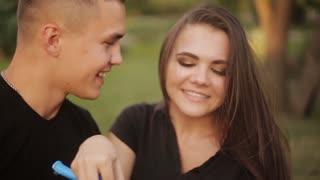 Pretty romantic couple in love having fun with soap bubbles in the nature