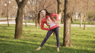 pretty young girl doing exercises on the grass in the spring park