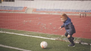 red-haired little boy playing with a soccer ball in the stadium