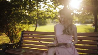 Romantic girl reading a book in the park