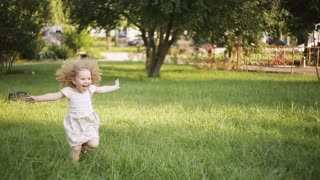 running little happy girl running on green meadow field