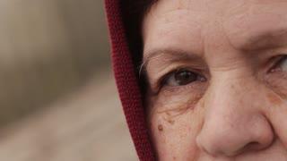 sad eyes of an elderly woman in a headscarf